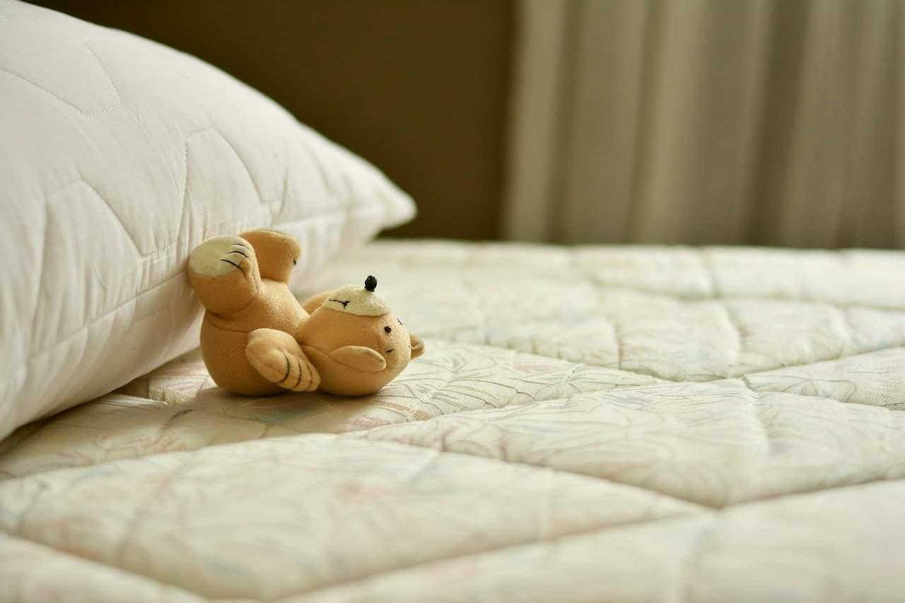 Little bear laying on a matress
