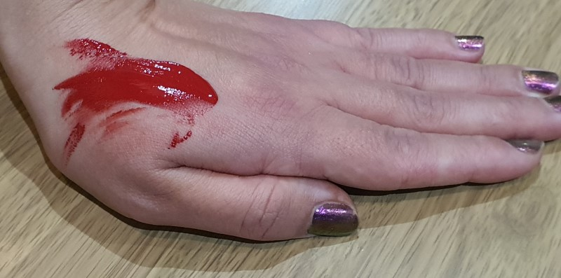 Red acrylic paint on hand